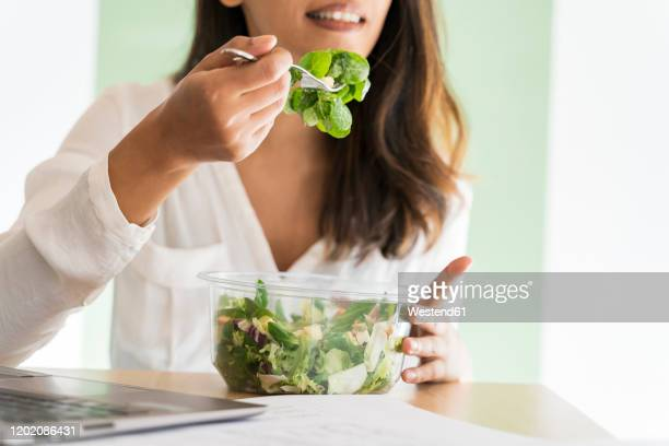 crop view of young architect eating mixed salad at desk - lunch stock pictures, royalty-free photos & images
