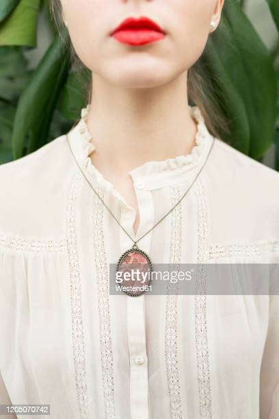 crop view of young woman wearing pendant on lace blouse - lace blouse stock pictures, royalty-free photos & images