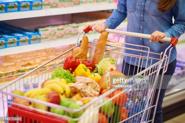 crop woman with cart full of food - full stock pictures, royalty-free photos & images