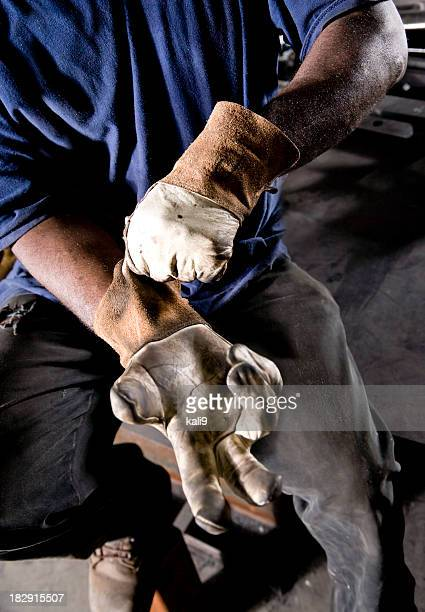 Cropped African American worker donning gloves