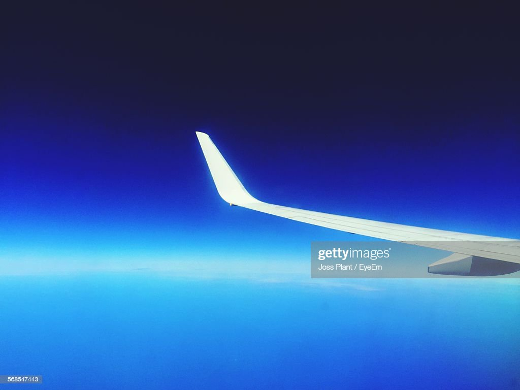 Cropped Airplane Flying In Clear Blue Sky : Stock Photo