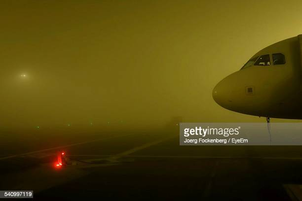 Cropped Airplane On Runway In Foggy Weather At Night