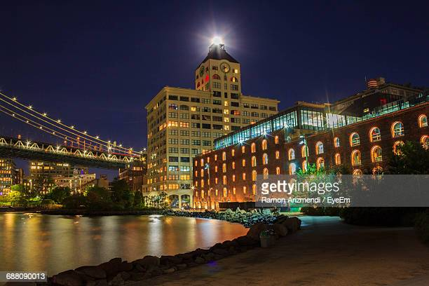 cropped bridge over river by illuminated clock tower at dumbo during night - clock tower stock pictures, royalty-free photos & images