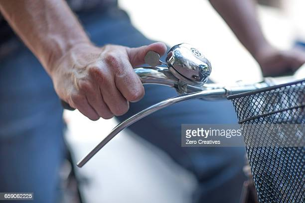 cropped close up of male cyclists hand ringing cycle bell - handlebar stock photos and pictures