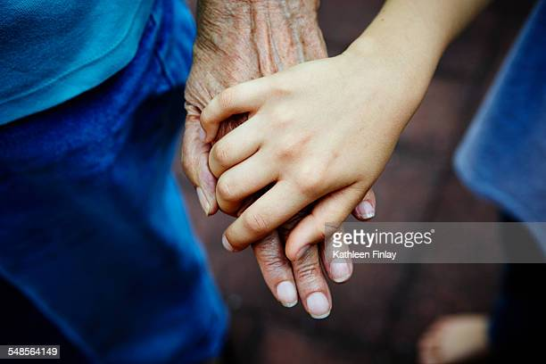 Cropped close up of senior woman and grandson hands touching in park