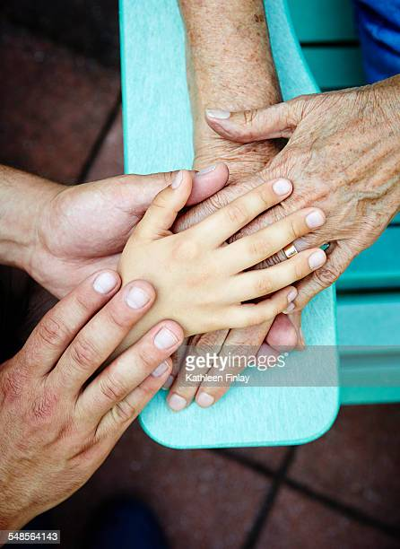 Cropped close up of senior woman, son and grandson hands touching each other in park
