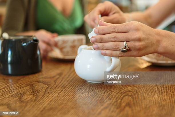 cropped close up of two mid adult female hands picking sugar from bowl in country store cafe - heshphoto photos et images de collection