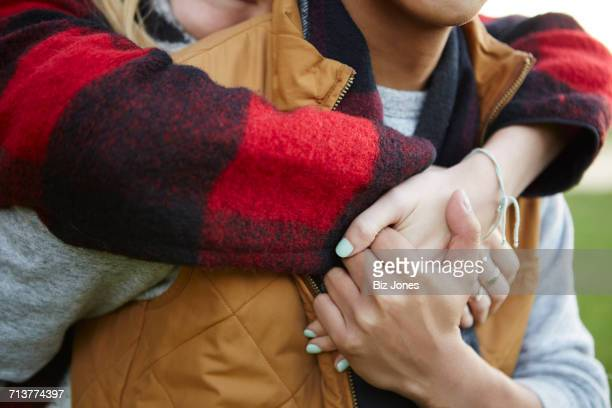 Cropped close up of woman hugging and holding boyfriends hands