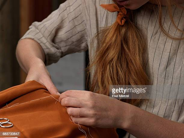 cropped close up of young female designers hands sewing orange fabric - zoom stockfoto's en -beelden