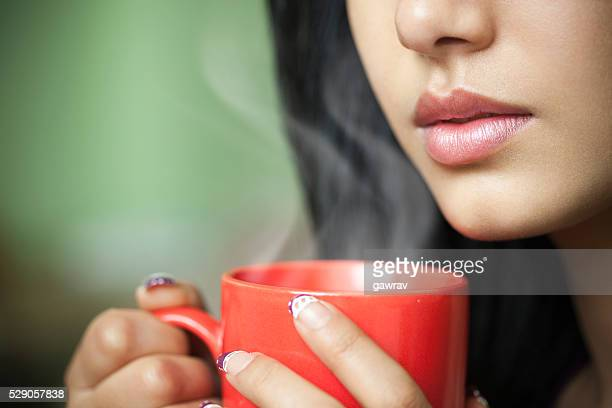 cropped close-up of young woman with hot steaming coffee mug. - hot tea stock pictures, royalty-free photos & images