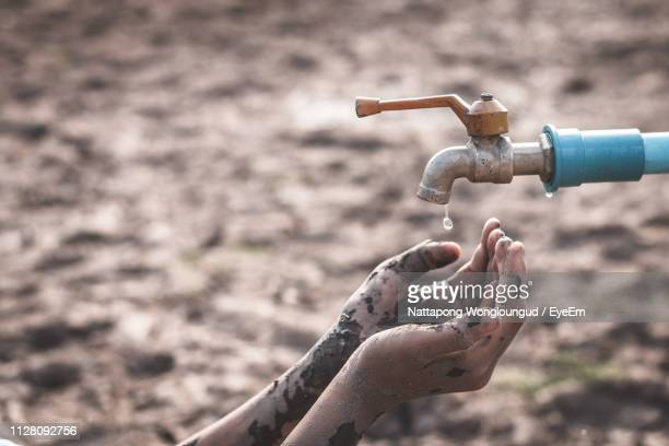 cropped dirty hands of person below faucet on barren land during drought - crisis stock pictures, royalty-free photos & images