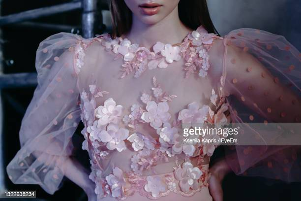 cropped figure of young beautiful model wearing pink fashion dress with flowers - fashion show stock pictures, royalty-free photos & images