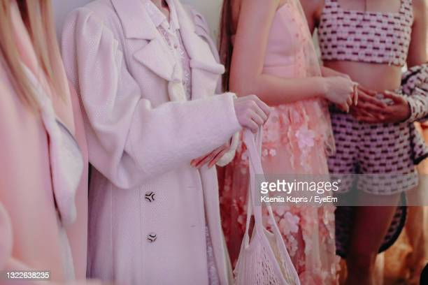 cropped figures of female models wearing pink and white fashion stylish outfits on backstage fashion - fashion week stock pictures, royalty-free photos & images