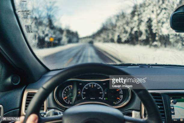 Cropped fingers of man driving car on road during winter