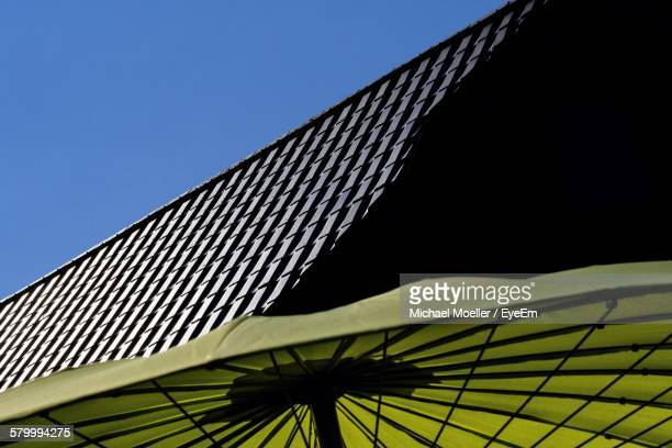 Cropped Green Parasol Against House Roof