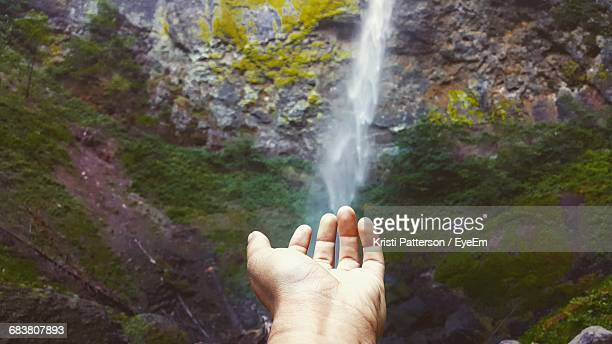 Cropped Hand Against Waterfall