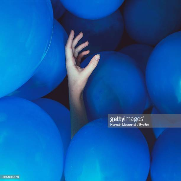 Cropped Hand Amidst Blue Balloons