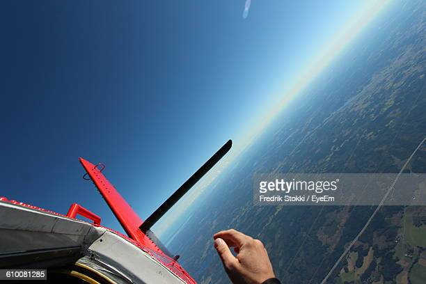 Cropped Hand And Airplane Against Clear Blue Sky