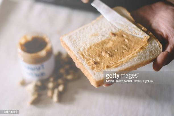 cropped hand applying peanut butter on bread - spreading stock pictures, royalty-free photos & images
