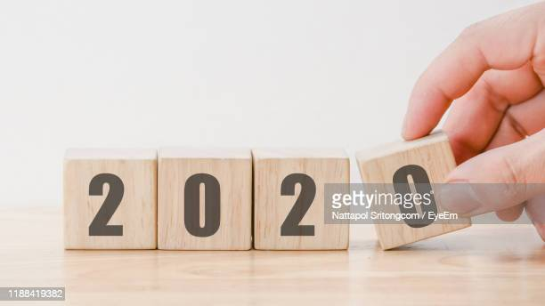cropped hand arranging blocks with 2020 number on table - 2020 calendar stock photos and pictures