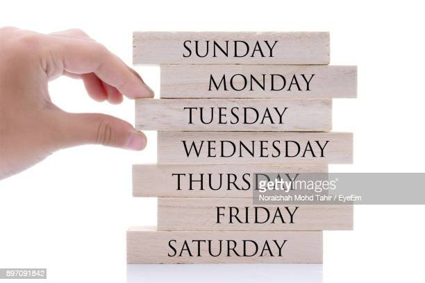 cropped hand arranging days of week over white background - tuesday stock photos and pictures