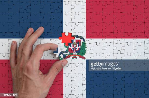 cropped hand arranging jigsaw pieces of dominican republic flag - dominican republic flag stock pictures, royalty-free photos & images