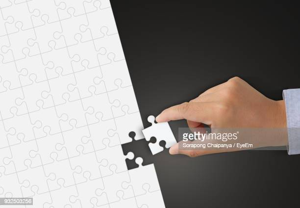 Cropped Hand Arranging Jigsaw Puzzle Over Black Background