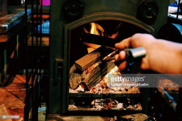 cropped hand burning wood in fireplace at home - wood burning stove stock photos and pictures