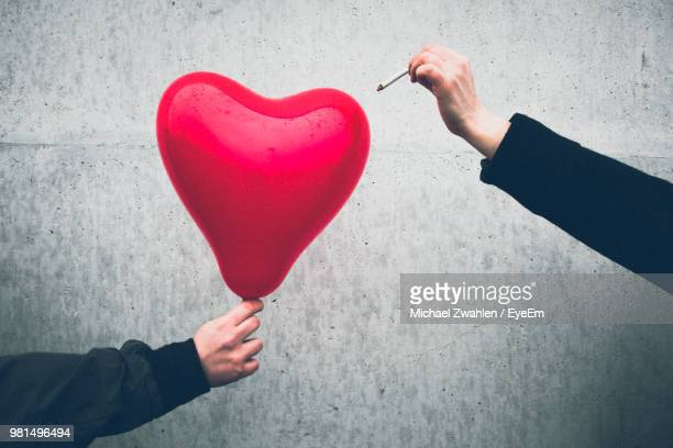 Cropped Hand Bursting Red Heart Shape Balloon With Cigarette Against Wall