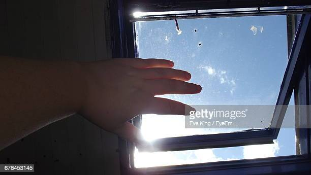 Cropped Hand By Ajar Window At Home