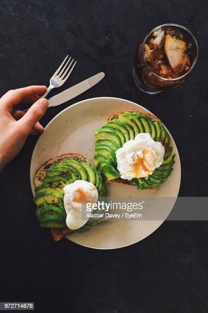 cropped hand by breakfast in plate on table - avocado toast stockfoto's en -beelden