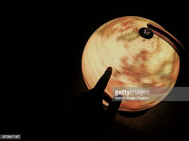 cropped hand by illuminated globe in darkroom - turning stock pictures, royalty-free photos & images