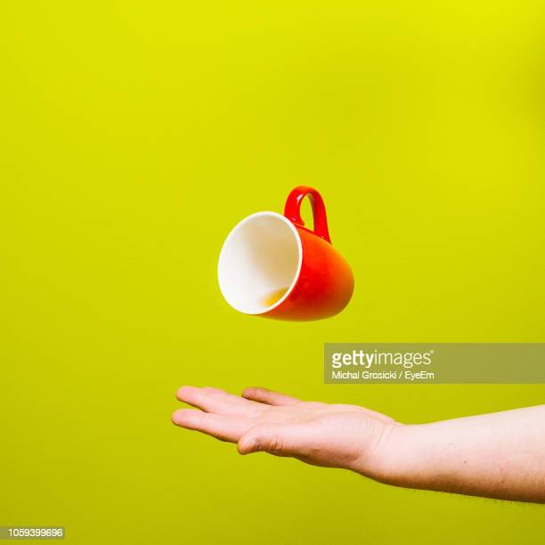 cropped hand catching red cup against yellow background - catching stock pictures, royalty-free photos & images