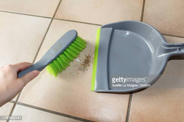 cropped hand cleaning dust on tiled floor - dustpan and brush stock pictures, royalty-free photos & images