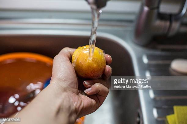 Cropped Hand Cleaning Peach In Kitchen