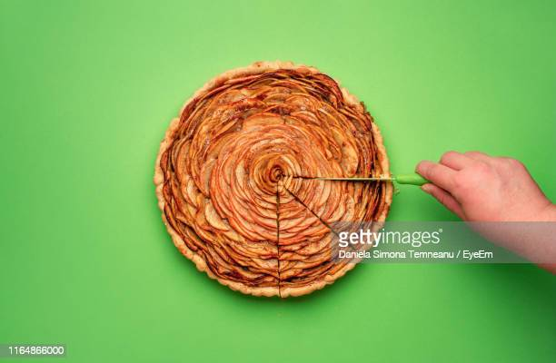 cropped hand cutting apple pie on green background - パイ ストックフォトと画像
