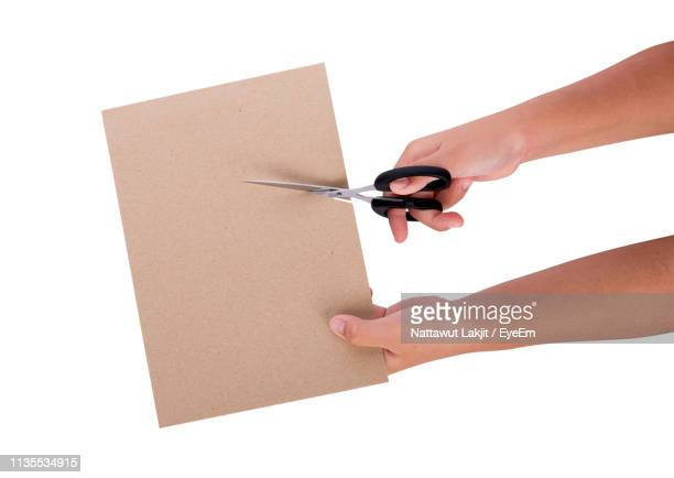 cropped hand cutting paper against white background - scissors stock pictures, royalty-free photos & images