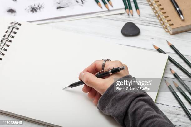 cropped hand drawing on note pad at table - florin seitan stock pictures, royalty-free photos & images