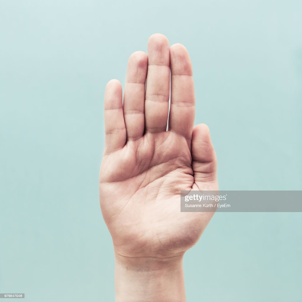 Cropped Hand Gesturing Against Turquoise Background : Stock Photo