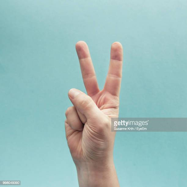 cropped hand gesturing against turquoise background - peace symbol stock photos and pictures