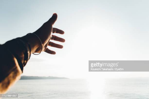 Cropped Hand Gesturing Towards Sea Against Sky During Sunny Day