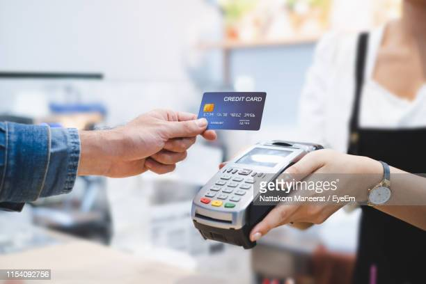 cropped hand giving card to woman in shop - credit card stock pictures, royalty-free photos & images