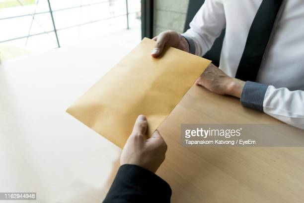 cropped hand giving envelope to businessman at table - corruption stock pictures, royalty-free photos & images