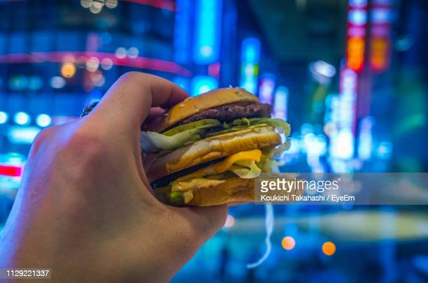 Cropped Hand Having Burger In Illuminated City At Night