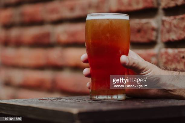 cropped hand having drink at table - pint glass stock pictures, royalty-free photos & images
