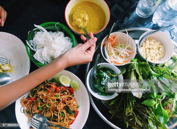 cropped hand having food at table - thai food stock pictures, royalty-free photos & images