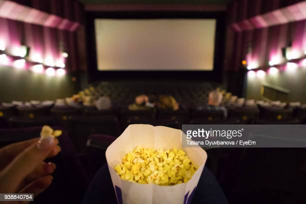 cropped hand having popcorns in theater - industrie du cinéma photos et images de collection