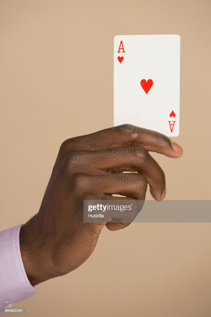 Cropped hand holding ace card against colored background : Stock Photo