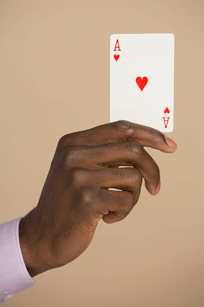 cropped hand holding ace card against colored background - human hand stock pictures, royalty-free photos & images