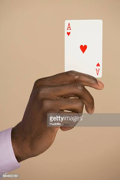Cropped hand holding ace card against colored background